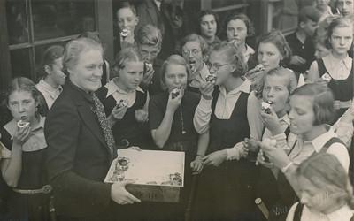 19381116 Onderschrift: En de taartjes waren reuze lekker. Op achterzijde: zie andere foto.  Opmerking: ook in compilatie.  Vlnr: Mieke Huizing, Cilia Ter Haar Romeny, Annet Coldeweij (met doos), Jopie Bekedam, Geert Houwink (tegen deurpost), Dick de Bie,  Jenny Zendijk, Willy Bryan, Sara van Esso (voor deurpost), Lien Tjeenk Willink (met taartje in mond), daarachter Dinie Blokker, Mieke ten Cate, Erika Staudt, Hannie Bloemendal, daarachter Truus Blaas, vooraan rechts Betty de Gaay     CollectieHorstBruijnzwartalbum Fotograaf; Van der Geijn  Formaat: 14 x 9  Afdruk zw