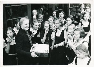 19381116 Onderschrift: Annet Coldewey (bestuurslid) taartjes voor de junioren! 25 jaar 1938. OOk 45 %. Dus deze foto is gereproduceerd, ws. voor Clubnieuws. Verder met potlood nr. 3. Dus serie.  Opmerking: zelfde foto als uit album vdHorst Bruijn, maar iets ruimer, iets meer personen. Deze foto staat in boek.    Collectie Coldewey afkomstig Annet Coldewey Fotograaf: v.d. Geijn  Formaat: 18 x 13 Afdruk zw