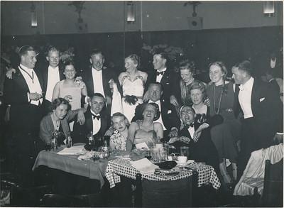 19391209 Onderschrift: geen  Achterop (tekst hoogstwaarschijnlijk van Hetty Stegeman): zie scan: 1939 Van links naar rechts (boven jwb):  Jan Broekhuis, Hanko de Koning, Hetty (Snoeck, jwb), Piet (Stegeman jwb), Paula Broekhuis, Bosgieter (ws. Jan Bosschieter, verloofde zich maart 1941 met Liesbeth ter Haar Romeny, jwb), Foukje Meyer (later Ten Velthuys), Annet Coldewey, Dick Knuttel Tweede rij: Bets de Koning (toen nog Houwing), Jan Peters, Frits Drijver, Lies ? Drijver (jwb:nee Riet Drijver, Lies was pleegdochter),  Onder: Ine  Peters, Let ? (mogelijk Zaalberg jwb) , Bob Meyer  Opmerking: achterop staat 1939. In het Clubnieuws heb ik geen groot groot feest in 1939 gevonden. Ik vermoed dat het geen privefeest is: Jan Broekhuis draagt het bestuurslint DHV. Zie foto receptie lustrum 1938. Piet Stegeman ging september 1939 in dienst en leerde daar Hetty Snoek kennen. Verloving einde winter 1939-1940 volgens Clunieuws maart 1940, gehuwd 12 juli 1940.  Mogelijk feest 9 december 1939 in Hotel De Wereld wegens bezoek 31 spelers en speelsters uit Haarlem en omstreken. Zie Clubnieuws december 1939 p. 30: Vanaf half negen zal er gedanst worden in Hotel De Wereld, dansmuziek van Be Dubbe's Swingquartet. Toegang voor leden en donateurs (trices) 75 ct. p.p. voor onze gasten natuurlijk gratis. In Clubnieuws januari 1940 verslag, Geen verdere informatie. Maar daarvoor in rok?? Kwamen Piet Stegeman en Hetty Snoek vrij onverwacht op het feest van 9 december 1939? Volgens dochter Arda Stegeman was de verloving januari 1940 (mal 21 augustus 2011). Kondigden zij hier een en ander aan?   In november 1939 was er m.i. geen lustrumfeest. Niets over in Clubnieuws.  Volledig identiek in Collectie Annet Coldewey. Achterop ook 46 en Hakeboom. Helaas verder niets.  Jan Blom staat er niet op. Als hij er geweest was, was hij er ws. bij geweest. Hij was toen gemobiliseerd. Ook Iet Resius staat ern iet op. Zij was net getrouwd en ws. vertrokken. Om deze redenen is 9 december 1939 tocht het meest w