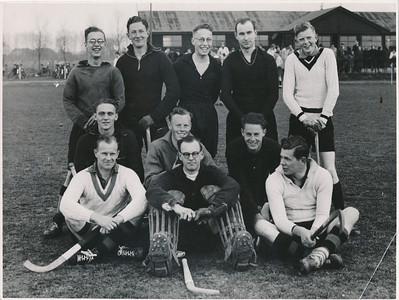 19410414elftalnr1 Onderschrift (grote foto): DHV I Oostelijk Hockey Kampioen 1940-1941 Opmerking: achterop deze foto  foto B - 1 50 % Gereproduceerd. Voor? In ieder geval voor Clubnieuws mei 1941 (Cliche Hockeysport) In Hockeysport 10 (1940-1941) 30 17 april 1941  p.1  met als onderschrift: Deventer oostelijk kampioen. Het elftal der Deventernaren dat het Oosten in de competitie om het kampioenschap van Nederland vertgenwoordigen zal. Foto Haakeboom (geen tikfout).   Ook dezelfde foto 30 x 21 met achterop sepia.  Zie ook andere foto in Archief Drijver iets ander moment. Foto ook afgedrukt in De Telescoop 1973 lustrumnummer p.13. Met als onderschrift: In 1941 werden we weer eens Oostelijk Kampioen.  Op basis van verslag in Hockeysport 17 april 1941 p.28 en 29, Deventer Dagblad 15 april 1941, Jaarverslag 1940-1941 in Clubnieuws september 1941 p. 98 en vergelijking met andere foto's, met name uit seizoen 1943-1944 kom ik tot de volgende namen:  Staand vlnr: Wim de Breuk, Bram Lammers, Jan Roelofsen, Henk Thomassen, Harmen van der Goot Knielend vlnr: Daan de Blocq van Scheltinga, Jan Derckx, Harry Derckx  Zittend vlnr: Joop Wagener, Jan Fesevur, Jan Broekhuis (volgens mij, Jan, maar nergens vermeld. Viel hij in?    ArchiefDHVlossefoto Fotograaf: Hakeboom Formaat:  24 x 18  Afdruk zw