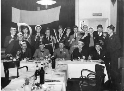 19410414diner1 Onderschrift: geen Achterop: S.A.D Album 1912-36 Opmerking: waarschijnlijk F.A.D. (Frits Albert Drijver).  Feest na afloop van het kampioenschap op 14 april 1941 in Hotel Royal. Zie uitvoerige beschrijving in Clubnieuws mei 1941 p.72/73.  Zittend vlnr: Bob Meijer (penningmeester, op zijn hoed 'kassier), Herman Ankersmit (op zijn hoed HA, hij ondertekende zo), Frits Drijver (op zijn hoed ''spullebaas''), Jan Blom (op zijn hoed 'fiedewiet' (zijn bijnaam: na een actie of toespraak werd er vaak gezongen 'Fiede Wiede wiet Jan Blom, analoog aan het toen bekende lied Columbus: Ér woonde in een heel ver land, wiede wiede wiet bom bom), Bob Alberts (scheidsrechtercommissaris met op zijn hoed Fluit1). Staande de elf spelers van het kampioenselftal, vlnr: Wim de Breuk,  Jan Fesevur, de keeper, met op zijn hoed 'De Zeef'',Henk Thomassen? met op zijn hoed de Hark, volgens Ijsbrand Rogge in mail ??? Henk Thomassen,  Harry Derckx, Jan Roelofsen, Bram Lammers, Jan Derckx met op zijn hoed 't Peerd'', Jopie Wagener met op zijn hoed 'Kappie'' zijn bijnaam (zie Clubnieuws), ?,.  Harmen van der Goot, ? met op zijn hoed 'de Logge'  Gescand door Hekkert 20100831 Gepubliceerd in Telescoop  jrg. 2 (2010-2011) nr. 1, p.25  CollectiearchiefDHV uit album Frits Drijver  Fotograaf: Hakeboom  Fotmaat: 24 x 18  Afdruk zw