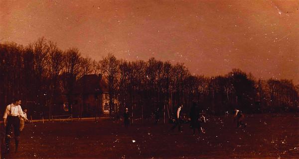 1921-1922 Onderschrift: geen Opmerking: veld Borgelerweg, zie andere foto. Deze foto bijna zelfde standpunt.  Wat later genomen (?), de zon gaat onder. Een paar spelers zijn naast de goal gaan zitten. De liggende fiets bij het hek is verdwenen. De fiets bij de boom staat er nog wel.   CollectieJanBlomIndischalbum Fotograaf: onbekend, ws. prive Formaat: 11 x 7 Afdruk zw