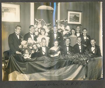 19231117  Onderschrift: 10 jarig bestaan van de D.H.V.  Opmerking: op  17 november 1923 in Flora in de Assenstraat. Zie Deventer Dagblad 19 november 1923. Zaterdagavond heeft de Deventer Hockey Club in 'Flora' haar 10en verjaardag gevierd. Vooraf had in een der achterzaaltjes een receptie plaats. Het bestuur getooid met geel-zwarte sjerpen der vereeniging zat er geflankeerd door een tweetal prachtige bloemstukken, huldeblijken van de Arnhemsche Hockey-Club en het Dev.- Landbouwcorps Nji-Sri. Van de Dev. Gymnasiastenvereen. had de jubilerende vereeniging een grooten theepot voor het veld, gevuld met chrysanten ontvangen.  ....... U.D. bood een vlag aan tijdens de receptie. De theepot staat links. De vlag ligt over de tafel. Rechtsachter het bloemstuk van AHC. En links achter van Nji-Sri.  Om half negen begon het feest. Frits Drijver sprak een welkomstwoord. Daarna huldigde M. Havelaar Frits Drijver namens de leden en bood een krans aan. Hij sprak de hoop uit dat als deze bladeren reeds vergaan zullen zijnde leden nog de herinnering mogen bewaren aan deze kranige linksback. De krans ligt voor Frits Drijver. Dus waarschijnlijk is er toen een foto gemaakt. Later op de avond bood ook PW DHV een krans aan.   Met de sjerpen dus het bestuur. Zittend vooraan: Vlnr:  ?, Frits Drijver,  In 1923 zaten in het bestuur volgens het overzicht uit 1938:  Frits Drijver, voorzitter, Mej. R.G. van Eldik, secretaris en J.P. Coelingh penningmeester.  Mogelijk dus onder vlnr? J.P. Coelingh, Mej. R.G. van Eldik, Frits Drijver en twee commissarissen, ws. een van de MKLS.  Foto R.G. van Eldik komt overeen foto Mevr. Koppius-Van Eldik bij het lustrum in 1938 (foto Dames Veteranen)      Boven vlnr: ?, Herman Ankersmit (T. Postma via  Annemiek Postma 4-4-2014), Marie (roepnaam Mieke) Ankersmit (zuster Herman Ankersmit, med. T. Postma 4-4-2014 via Annemiek Postma, en dus moeder Toos Postma-Van Houten, zij is geboren 28-2-1899 en hier dus 23 jaar), ?, ? ?, ?     Collectie Postma-Van Houten Fotogra