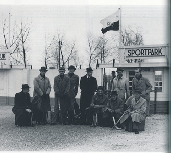 19420406 Onderschrift: 1942: Herenteam bij uitwedstrijd in Deventer. Opmerking: hoogstwaarschijnlijk het Veteranenteam van Schaerweijde. Dat speelde op maandag 6 april 1942 een wedstrijd in Deventer voor de Veteranenbeker. Deventer won met 3-0. Zie verslag Deventer Koerier 7 april 1942. Dit was niet de ingang van de velden van de DHV, maar die van het Gemeentelijke Sportpark. Daar speelde toen kennelijk Labor. Zie vlag en bordje. Het team wacht daar mogelijk op een bus. Zie ook Hockeysport. Deze wedstrijd was meermalen verplaatst.        Gedenkboek Schaerweijde 2007, p. 38. Fotograaf: onbekend Formaat: 21 x 19 Afdruk zw