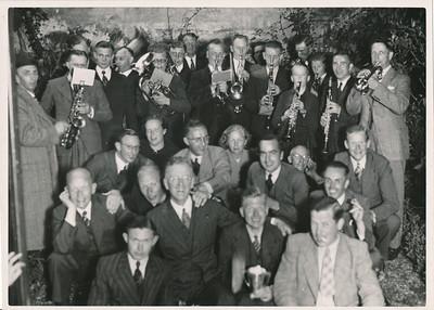 19420517 Geen onderschrift Vlnr: Henk Vervoort, Jan Verburg, Van Drooge, H.J. Ankersmit, Bob Meijer, Jan Blom (met beker), Chris van der Mandele, Dr.J. Houwink, Jan Broekhuis, Jan Peters, Piet Stegeman. Deze opstelling komt volledig overeen met de elftalfoto in Hockeysport 21 mei 1942. Vandaar de datering 17 mei 1942.  Zie ook Clubnieuws November 1966 p. 16 en 17 artikel van  van Jan Peters: en het feest bij Nera Demmers was, inclusief de Deventer Harmonie, uitbundig. Dus in De Keizerskroon. Vooraan en achteraan ws. eerste elftalspelers.Of bestuursleden?   Klopt dit met veterenelftal? In ieder geval 11 man!   JanBlomcremealbum losse foto Fotograaf: Van der Geijn Formaat: 17 x 13 Afdruk zw