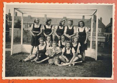 19430314 Onderschrift: D.H.V. Kampioen 1943 Opmerking: nog niet gevonden Deventer Dagblad Weinig over damescompetitie.  Waar? Niet in Deventer. Links staand Paula Broekhuis, keepster is Hannie Bloemendal.  Hockeysport 12 (1942-943) nr. 26 11 maart 1943: We schieten nu goed op met deze  noodcompetitie, de zoo gewenschte afwerking zal echter wel uitblijven en zoo verwachten we Zondag aanstaande Deventer kampioen te zien worden, want de Deventer Dames zullen zicht toch zeker niet in Enschede, thans door E.H.V., niet voor de tweede maal de kaas van het brood laten eten, ....  Toelichting pagina daarvoor: Deventer verloor onverwacht op 7 maart in Enschede van P.W. met 2-0.  Dis daarom gedateerd 14 maart 1943. En bij E.H.V. dat zou kunnen. Van deze wedstrijd nergens verslag gevonden.   ArchiefDHVlossefoto Fotograaf: onbekend Formaat: 9 x 6 Afdruk zw