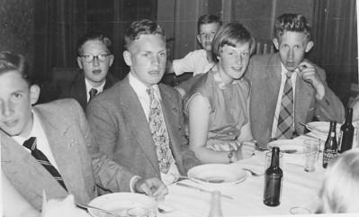 """19550430  Onderschrift in mail Jan van der Eijken 29 maart 2012: feest 6 mei 1955 omdat heren 1, 2 en 3 kampioen waren geworden. Vlnr aan tafel: Hans Smoor, Gait Broekhuis, Marga Riesebos, Jan van der Eijken. Op de achtergrond rechts Ruud Krom. Einde citaat. Opmerking: volgens Clubnieuws 16 (1955) nr. 5 mei 1955 """"""""besloot het besuur onmiddellijk op Zaterdag 30 april een maaltijd te organiseren ..... Op Zaterdag  30 april dus groots feest ... ... werd een eenvoudige maaltijd gebruikt""""Dus ws. foto op 30 april 1955.   CollectieJanvanderEijken Fotograaf: onbekend Formaat: onbekend, per mail ontvangen Afdruk zw"""