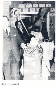 19661209 Onderschrift: zie foto Opmerking: blijkens de tekst kwam de Sint binnen op een levensgroot paard .... maar dan toch wel met kop en staart. Waarschijnlijk karretje. Links Dick Ypes, daarachter Appie Kolkman.  Clubnieuws 28 (1966-1967) 1 (januari) p.8