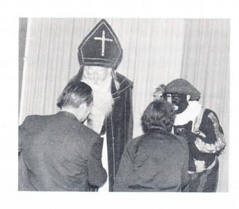 19661209 Onderschrift: Vraag: Wie zijn deze dame en heer, die St. Nicolaas en Zwarte Piet begroeten op het St. Nicolaasfeest december 1966?  Opmerking: In volgende Clubnieuws p. 28 de oplossing: De heer en mevrouw Kolkman begroeten Sint Nicolaas. Hans Noor Swaefkenstraat 5 Deventer won de prijsvraag en kreeg een waardebon.   Clubnieuws 28 (1966-1967) 2 (mei) p, 28