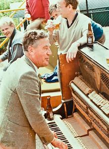 19850518  Arie van Noortwijk achter de piano  Op de achtergrond: vlnr: Ton Stoffel, ? roode trui, ? bl;auwe trui (Han Ypes??),dan Frans Wennekendonk Mededeling Riet van noortwijk 11 april 2014: Frans Wennekendonk herkende zich op deze foto. Hij was lid van een feestelftal uit Utrecht, mogleijk Kampong. Frans maakte op verzoek collage van de foto's van Arie, kort na Aroe's dood in ?? Frans was beroepsfotograaf. Hij is vrij snel daarna overleden.  Anne van der Horst Bruyn bracht toen deze foto voor de collage, Frans herkende zich . JWBlom: daarom moet dit bij het Koekternooi zijn geweest. Het Koektoernooi was op 18 en 19 mei 1985. Daarom nu zo gedateerd.  Volgens weerverleden was het zaterdag mooi weer, zondag wat minder. Daarom mogelijk zaterdag.   Voorwerpen aanwezig Clubhuis 7 maart 2013  Fotograaf: Lucrees van Groningen