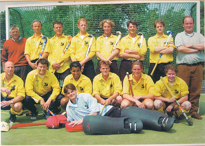 Onderschrift:  Heren I promotieteam van 2de naar de 1ste klasse seizoen 2002-2003  V.l.n.r. staand: Huib van laar (coach), Steven Bos, Hidde Hartog, Esli Wessels, Anthony van Kesteren, Epco Koekebakker, Thiemo Bruning (aanvoerder, trainer), Merlijn van Loon (ass. coach, manager), V.l.n.r. zittend: Arnout Nefkens, Ivo Zernitz, Jip Hogenelst, Coen Hartog, Robert Bos, Wijnand Went,  Liggend: Marnix Bakker  Clubhuis in lijst Fotograaf: onbekend Formaat: 28 x 20 Afdruk kleur