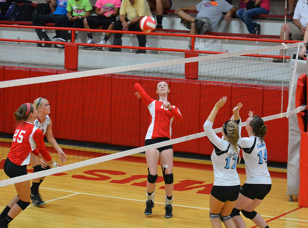 Effingham's Chandler Ramey looks to spike the ball over the Cumberland defense of  Cumberland's Jenna McMechan (12) and MacKayla Sowers (14).
