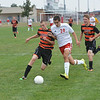 Effingham's Tyler Katz (20) battles Olney's Andrew Steber (14, left) for a loose ball near the Olney goal, while Trystin Runyon (5) trails the play in support of Steber.