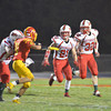 Effingham's Zach Miller (32) carries the ball with a lead blocker in Travis Durbin (21), while Khye Heuerman (60) blocks Charleston's Chase Black (81) in Charleston. The Flaming Hearts earned their first victory with a 26-13 win.