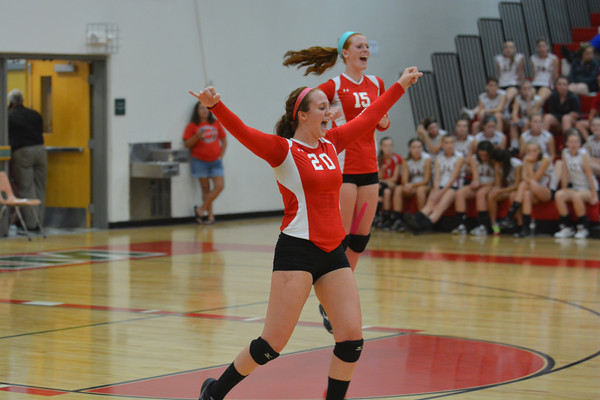 Effingham's Josie Zerrusen (20) celebrates a point while Chandler Ramey (15) celebrates in the background against Charleston.
