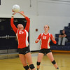 Effingham's Felicia Totten (25) backs up and sets the ball for a teammate while Chandler Ramey (15) looks on at Teutopolis High School.