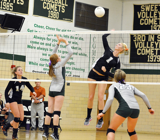 Altamont's Gabby Alwardt goes up for a kill while Stew-Stras' Morgan Stremming (9) and Baylee Quast (23) defend.