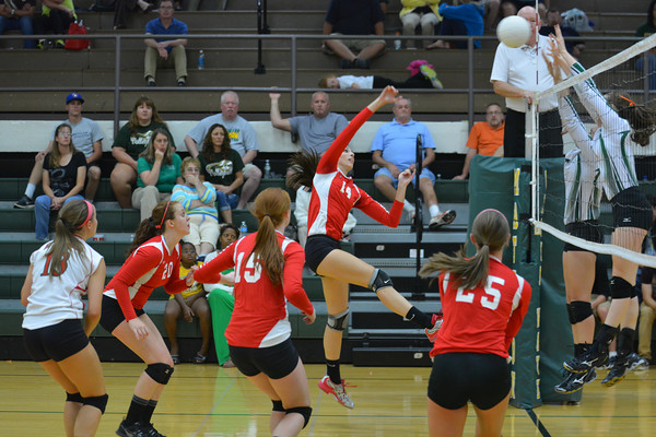 Effingham's Brittany Beals (14) rises up among a host of Effingham teammates for a spike over the Mattoon block at Mattoon.