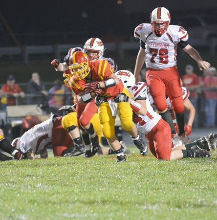 Effingham's Griffin Paige (34) wraps up Charleston's Myles Decker (6) near the line of scrimmage during the Flaming Hearts' 26-13 win over the Trojans in Charleston.