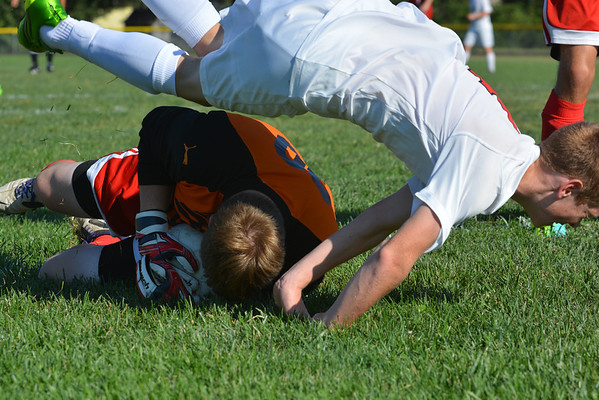 Effingham goalie Frank Kasdorf (orange) dives on a loose ball in front of the net and holds on while St. Anthony's Donovan Hammer (white) flies over him after being tripped up in an effort for the loose ball.