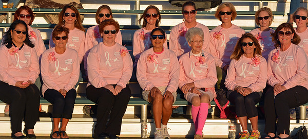 Breast cancer survivors wait to escort the varsity players onto the field for introductions before the game.
