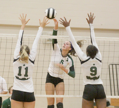 Leah Daniel goes up for a kill between two Westfield players on Thursday.