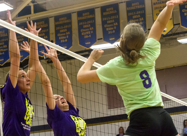 St. Anthony's Meg Richards (right) goes up for a hit as Teutopolis' Jessica Drees (left) and Macy Michels (center) go up for the block.