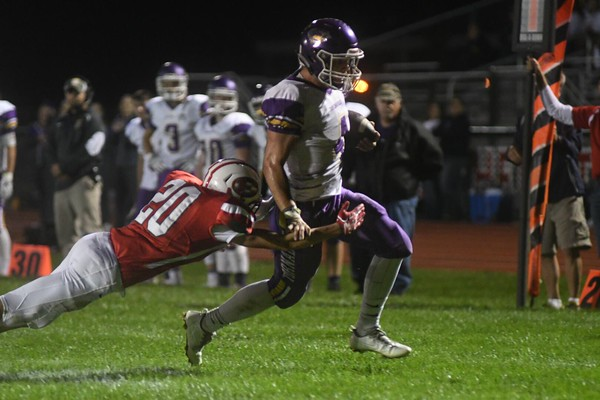 Effingham's Kendall Ballman dives to tackle Taylorville quarterback Parker Stokes in the first half at Klosterman Field.