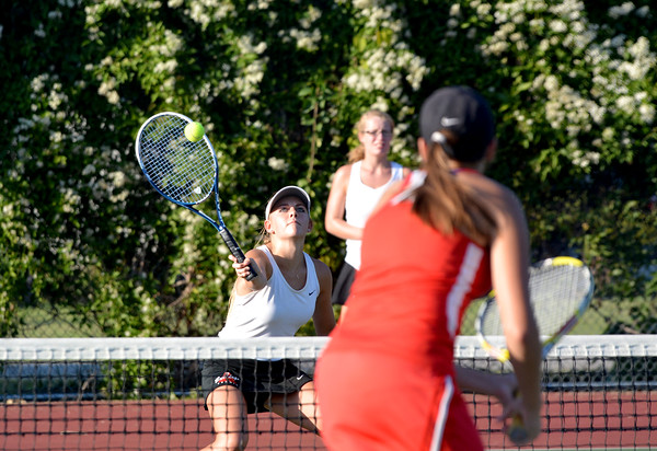 St. Anthony's Mary Claire Wegman (left, crouching) plays a ball at the net while teammate Emilee Mossman (far background) and Effingham's Skyler Schafer (red, foreground) watch during a match at Community Park.