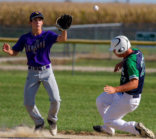 Brownstown/St. Elmo's Isaac Maxey (left) receives the throw from catcher Landon Feezel during Isaac Kramer's steal attempt at second base.