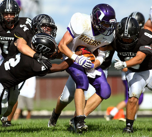 9-8-12<br /> Western HS vs Northwestern HS Football<br /> Northwestern's Trenton Brazel weaves between the defense near the goal line with Western's Kendal McDonald trying to strip the ball in the 3rd quarter.<br /> KT photo | Tim Bath