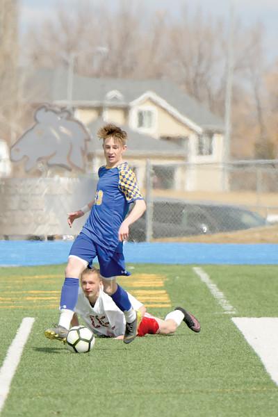Matthew Gaston | The Sheridan Press<br>Sheridan's Carter Wells (13) beats his man moves the ball down field Saturday, March 30, 2019.