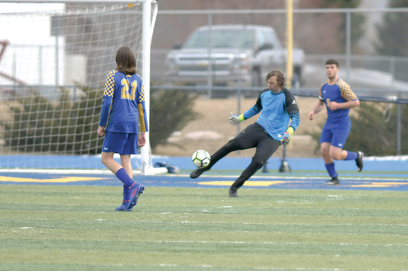 Matthew Gaston | The Sheridan Press<br>Sheridan's Sam Salyards punts the ball down the pitch after blocking a shot by Cheyenne East at Homer Scott Field Friday, March 29, 2019.
