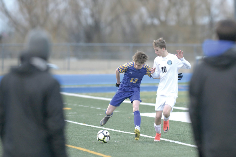 Matthew Gaston | The Sheridan Press<br>Sheridan's Carter Wells (13) brings the ball down the pitch under pressure from Cheyenne East's Carter Rich (10) at Homer Scott Field Friday, March 29, 2019.