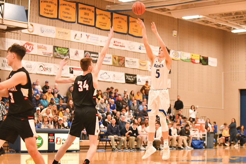 "Matthew Gaston | The Sheridan Press<br>Sheridan High School's Gus Wright (5) shoots for three over Cheyenne Central's 6'11"" forward Lawson Lovering (34) Friday, Feb. 1, 2019."