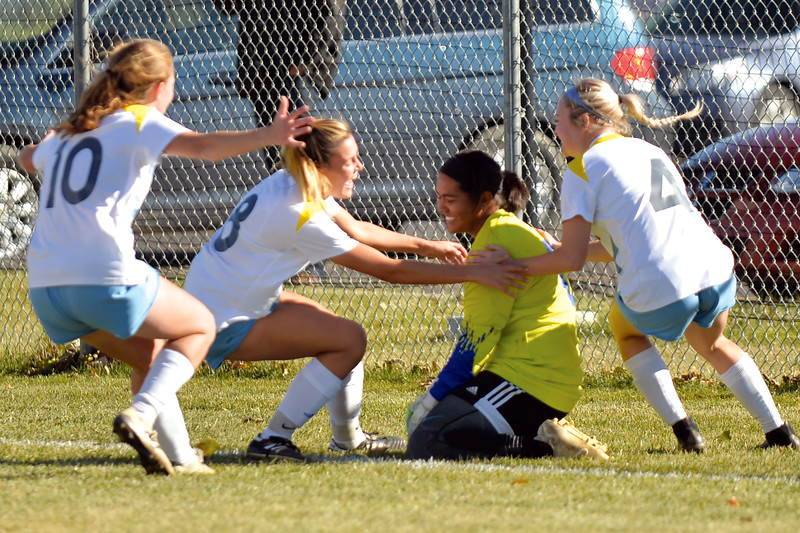 Joel Moline | The Sheridan Press<br /> Sheridan College's goalkeeper Karla Gaytan (0) is swarmed by teammates Chezney Mamalis (4), Hannah Dalebout (8), Casey Wassum and the rest of the team following the penalty kick victory over Trinidad State Junior College, Friday, Oct. 25, 2019.  Gaytan had two saves during penalty kicks to help the Lady Generals earn the playoff win.