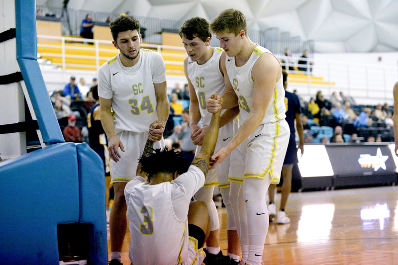 Joel Moline | The Sheridan Press<br /> Sheridan College's Jaren Fritz (34), Hayden Petersen (0) and Tristan Bowers (23) helps teammate JoVon McClanahan (3) of the floor during the game against Laramie County Community College Saturday, Jan. 18, 2020.
