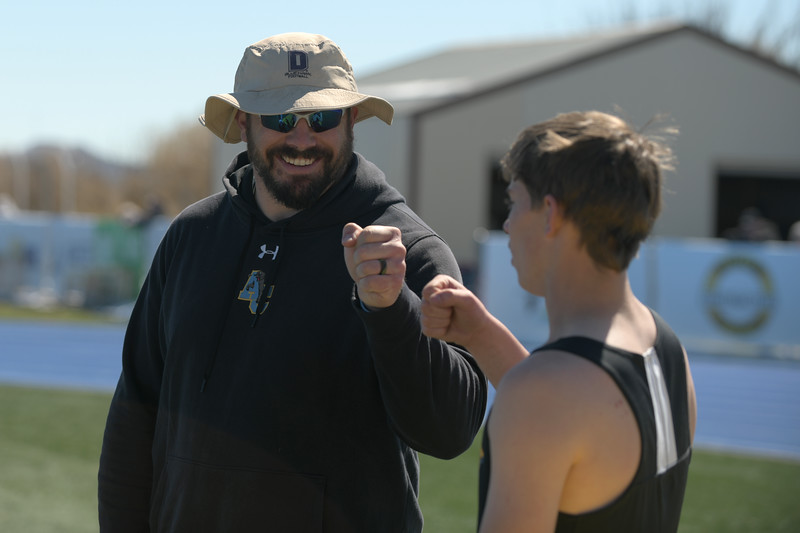 Matthew Gaston | The Sheridan Press<br>Arvada-Clearmont coach Ross Walker fist bumps Torrey Veach after Veach's final triple jump attempt Saturday, April 13, 2019.