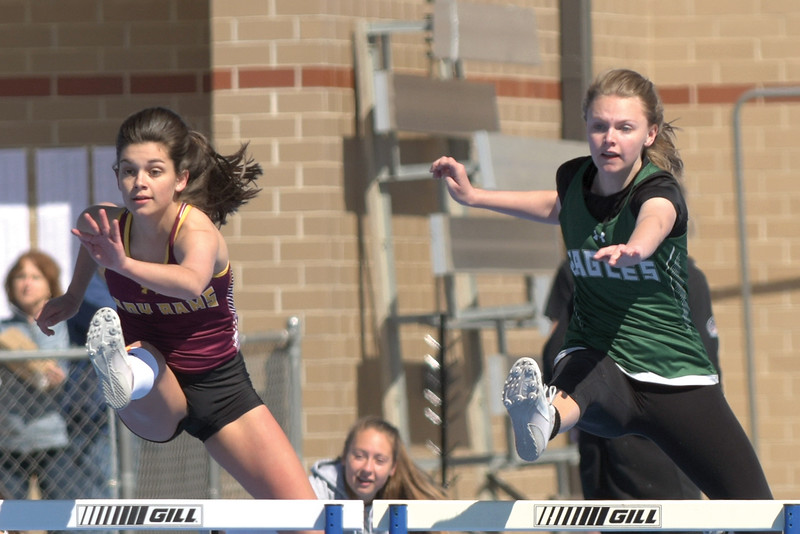 Matthew Gaston | The Sheridan Press<br>Big Horn's Torie Greenelsh, left, and Tongue River's Jane Pendergast hit the first hurdle of the 100m hurdles in stride with one another at Homer Scott Field Saturday, April 13, 2019.