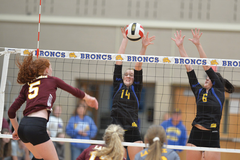 Bud Denega | The Sheridan Press<br /> Sheridan's Mckailyn Malles, left, and Madyson Godwin rise for a block during a game against Laramie at Sheridan High School Saturday, Oct. 13, 2018.