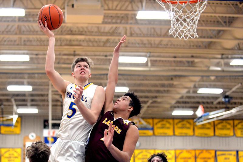 Joel Moline | The Sheridan Press<br /> Sheridan's Gus Wright (5) scores despite the tight defense against Laramie High School Saturday, Feb. 15, 2020.