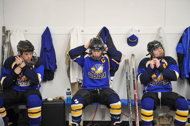 Justin Sheely | The Sheridan Press<br /> Sheridan's Jack Chase, left, Sam Boyles and Toby Jacobs, right, strap their head gear on in the locker room during the WAHL High School B State Tournament at Whitney Ice Rink in the M&M's Center Saturday, Feb. 24, 2018.