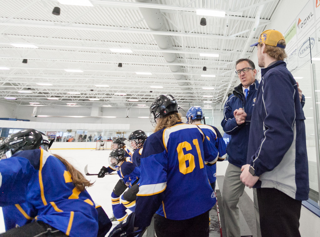 Tibby McDowell | The Sheridan Press<br /> The Sheridan Hawks rush the ice at the final buzzer as coaches John Chase, left, and Kirk Viren exchange a congratulatory handshake during the semi-finals of the state tournament at Whitney Rink at the M&M's Center Saturday Feb. 24, 2018.  The Sheridan Hawks advance to the finals with a 3-2 win over the Pinedale Glaciers.