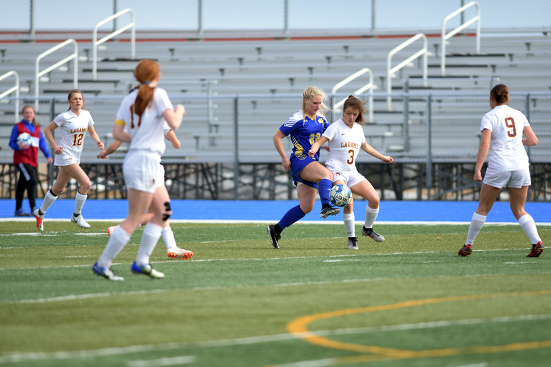 Matthew Gaston | The Sheridan Press<br>Sheridan's Braylee Standish (22) gets the quick touch to take control of the ball despite being blocked at Homer Scott Field Saturday, March 23, 2019.