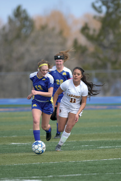 Matthew Gaston | The Sheridan Press<br>Sheridan's Courtney Wallach (13) brings the ball down the pitch under pressure during play against Laramie Saturday, March 23, 2019.