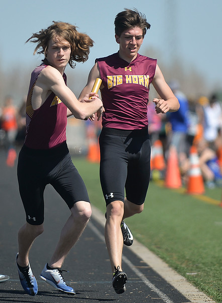 Justin Sheely | The Sheridan Press<br /> Big Horn's Kobie Cummins, left, exchanges with Noah Harvey in the 1600-meter medley relay during the Dan Hansen invite at Sheridan High School Saturday, April 21, 2018.