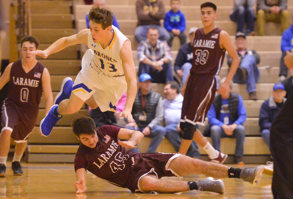 Justin Sheely | The Sheridan Press<br /> <br /> Sheridan's Noah Erickson leaps over Laramie High School's Nathan Burma at Sheridan High School Friday, Jan. 19, 2018. The Broncs cruised past the Plainsmen 71-36.