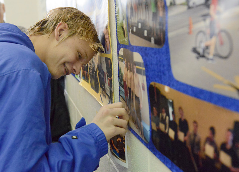 Justin Sheely | The Sheridan Press<br /> Sheridan's Thomas Yates adds a photo to the senior photo board during the last home swim meet at Sheridan Junior High School pool Friday, Jan 26, 2018.
