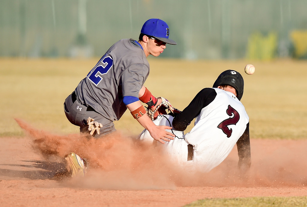 . Broomfield High School\'s Trenton Harris (No. 12) can\'t make the tag on Silver Creek High School\'s Spencer Rich (No. 2) in Longmont, Colorado on March 12, 2018. (Photo by Matthew Jonas/Staff Photographer)