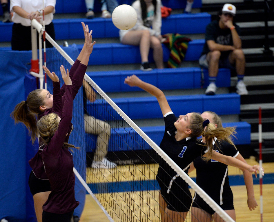 . LONGMONT, CO: September 18: Longmont\'s Caroline Demosthenes trie to hit past Silver Creek\'s Caitlin Volkmann and Kaitlin James. Silver Creek played Longmont at LHS on September 18, 2018.  (photo by Cliff Grassmick/Staff Photographer).